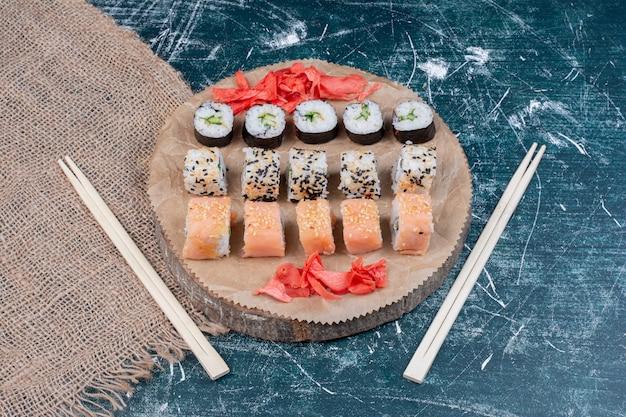 Assortiment de rouleaux de sushi servis sur un plateau en bois avec du gingembre mariné et des baguettes.