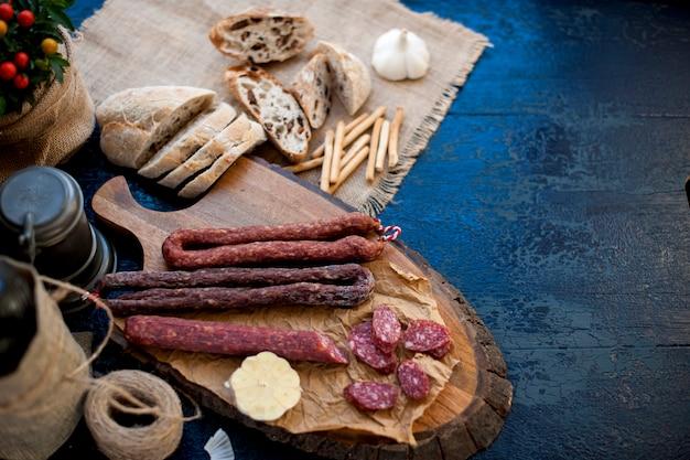 Assortiment de salami sur une planche de bois et du pain