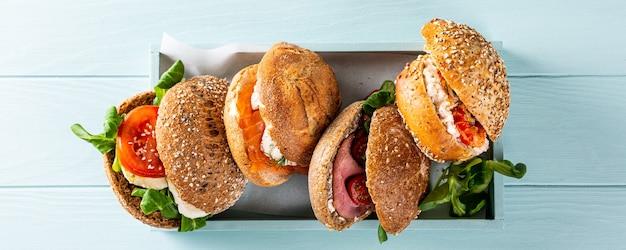 Assortiment de sandwichs dans une boîte en bois sur une surface en bois bleue. concept d'aliments sains avec espace copie