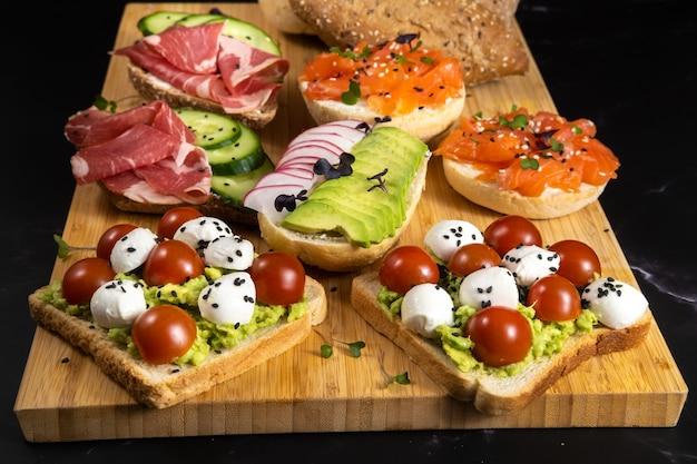 Un assortiment de sandwichs avec du poisson, du fromage, de la viande et des légumes était posé sur la planche et un petit pain.