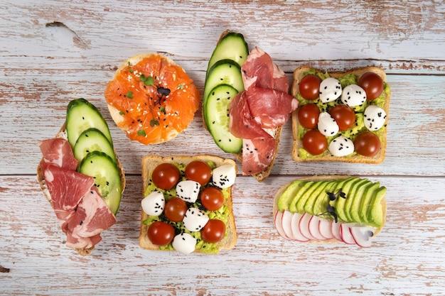 Un assortiment de sandwichs avec du poisson, du fromage, de la viande et des légumes était posé sur la table en bois.