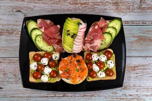 Assortiment de sandwichs avec du poisson, du fromage, de la viande et des légumes sur une plaque noire et un fond en bois.