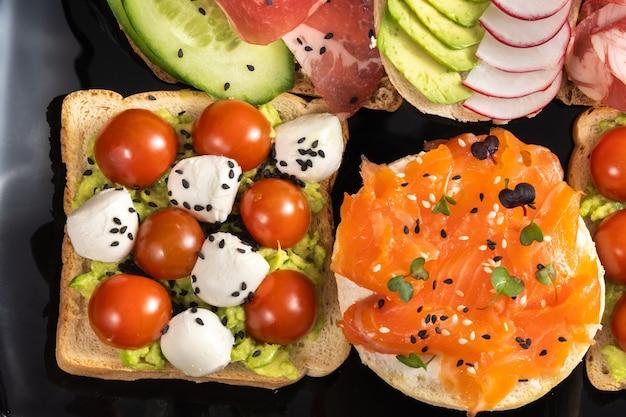 Assortiment de sandwichs avec du poisson, du fromage, de la viande et des légumes sur une plaque noire.