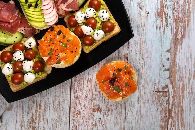 Assortiment De Sandwichs Avec Du Poisson, Du Fromage, De La Viande Et Des Légumes Sur Une Plaque Noire Photo Premium