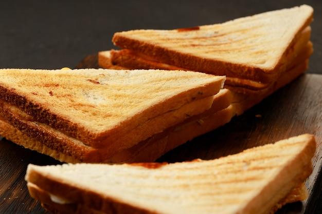 Assortiment de sandwichs triangulaires grillés sur planche de bois close up