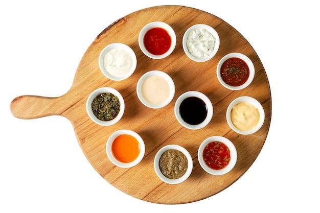 Assortiment de sauces dans des bols sur une planche de bois