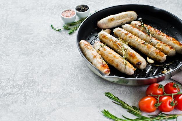 Assortiment de saucisses frites dans une poêle à frire, porc, bœuf, poulet, dinde.