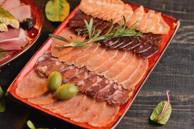 Assortiment de saucisses, jambon et jambon avec des tranches de pain frit sur une plaque rouge. sur une table en bois