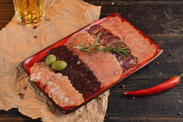 Assortiment de saucisses tranchées sur une plaque rouge. avec un verre de bière. sur une table en bois