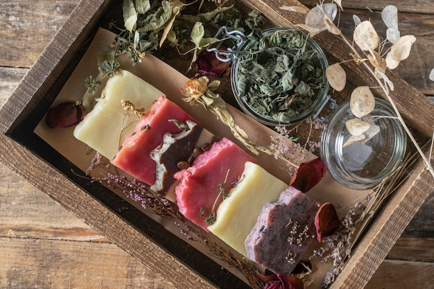 Assortiment de savons cosmétiques faits à la main sur une table en bois.