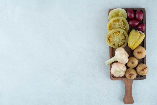 Assortiment de savoureux légumes fermentés sur planche de bois.