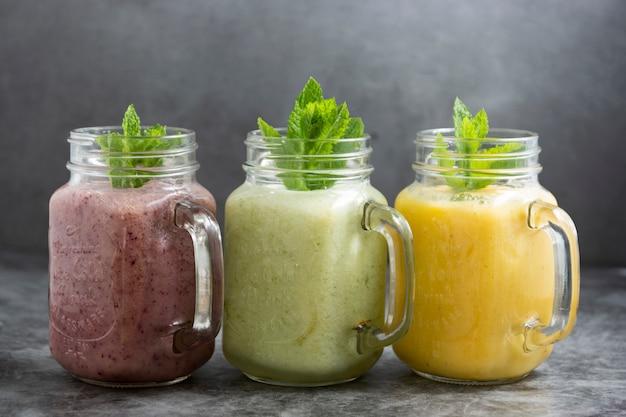 Assortiment de smothie aux fruits dans des bocaux en verre, boissons rafraîchissantes d'été.