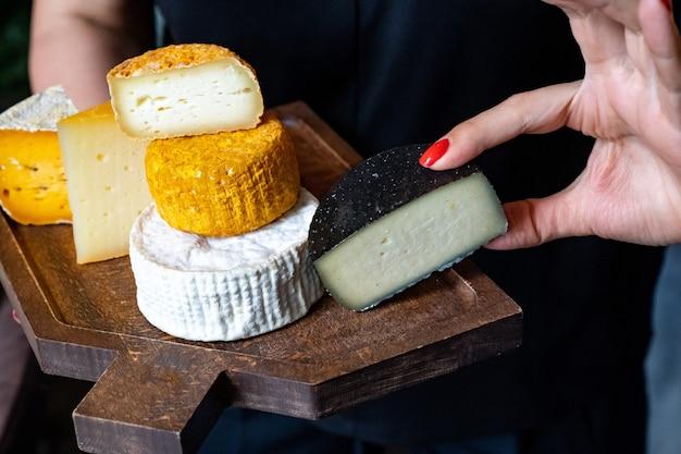 Assortiment de têtes de fromage sur une planche à découper dans les mains d'une femme.