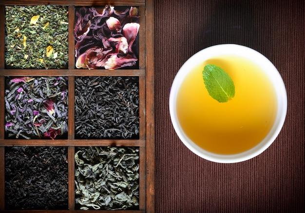 Assortiment de thé sec dans une boîte en bois avec une tasse blanche