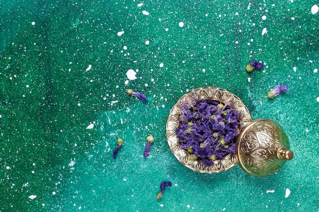 Assortiment de thé sec dans des mini assiettes vintage dorées. types de thé