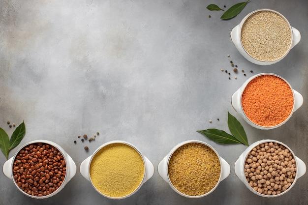 Assortiment varié de céréales (quinoa, lentilles, pois chiches, boulgour, couscous, haricots) et d'épices,