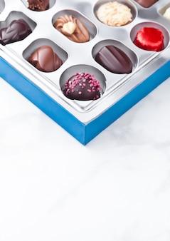 Assortiment de variétés de bonbons de luxe au chocolat blanc et noir dans un plateau en plastique plastick sur fond de marbre