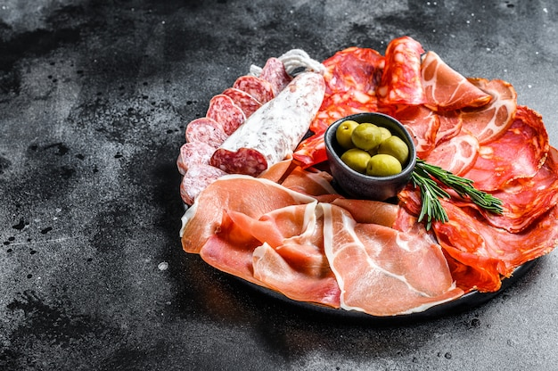 Assortiment de viandes froides espagnoles. chorizo, fuet, longe, jambon ibérique, olives. surface noire. vue de dessus. espace copie