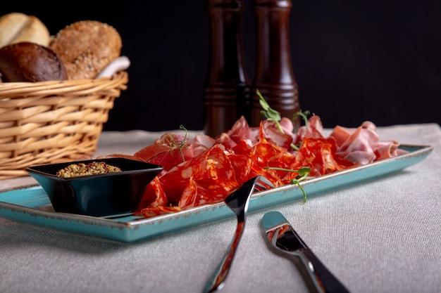 Assortiment de viandes froides, prosciutto, tranches de jambon, boeuf séché, salami, viande et moutarde sur fond noir. apéritif à la viande, concept de restauration.
