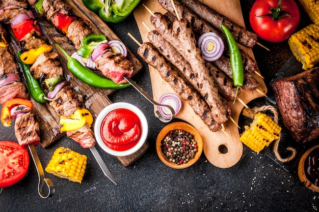 Assortiment de viandes de grillades de grillades variées, bbq party fest - shish kebab, saucisses, filet de viande grillé, légumes frais, sauces, épices, table en béton rouillé foncé, au-dessus de l'espace de copie