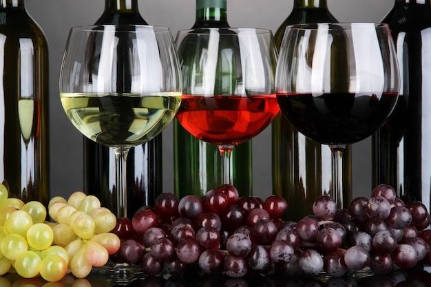 Assortiment de vin dans des verres et des bouteilles sur fond gris