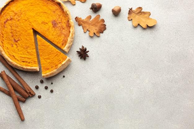 Assortiment vue de dessus avec tarte à la citrouille en tranches et feuilles