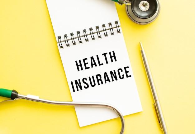 Assurance maladie écrit dans un cahier sur une table de couleurs