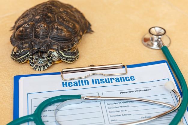 Assurance maladie avec stéthoscope de formulaire de réclamation d'assurance et tortue rousse