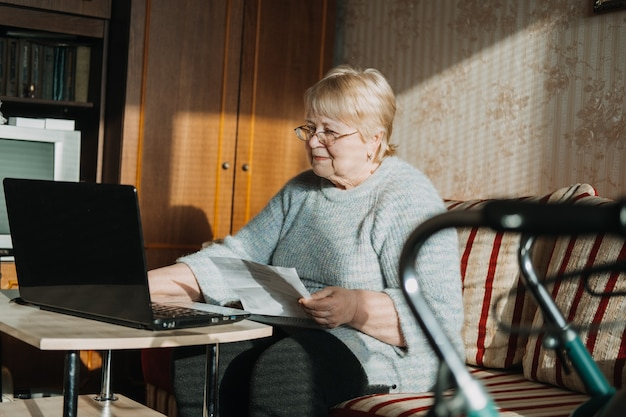 Assurance-vie police d'assurance médicale d'invalidité pour les personnes âgées femme mûre dans des verres avec un ordinateur portable