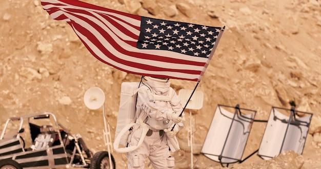 Astronaute avec drapeau américain debout sur les montagnes rocheuses de l'alien red planet / mars. première mission habitée sur mars