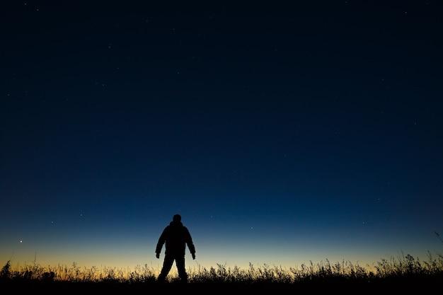 Astronome et ciel étoilé de nuit sur une surface d'un horizon crépusculaire