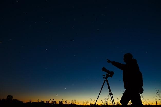 L'astronome photographie le ciel étoilé de la nuit sur un appareil photo numérique à l'aide d'un trépied.