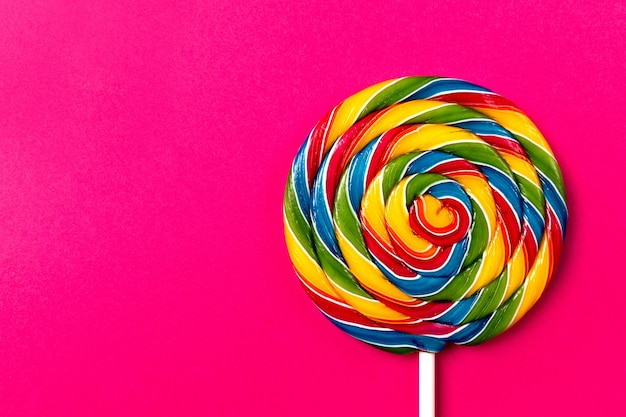 Astucieux et appétissant party accessoire sweet swirl candy lollypop sur fond rose vue de dessus