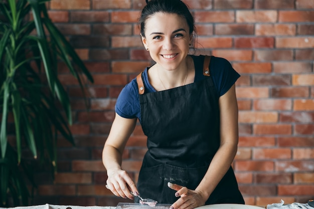 Atelier d'artiste. artisanat d'argile en cours. souriante jeune femme avec des outils de modélisation sur le lieu de travail en regardant la caméra.