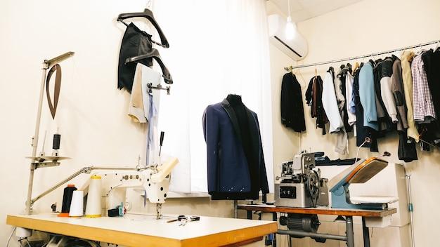 Atelier de couture, studio solaire. tissus colorés, vêtements visibles.