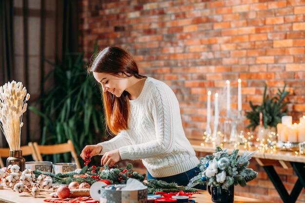 Atelier de fleuriste. dame créative travaillant sur une nouvelle décoration d'hiver festive.