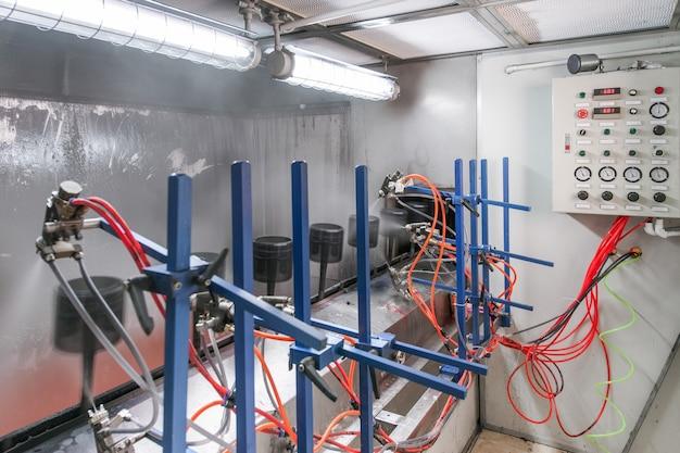 Atelier mécanique de peinture de détails sur une bande transporteuse à travers un flacon pulvérisateur