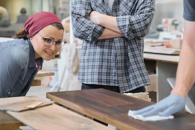 Atelier de menuiserie, ouvrier vernissant une étagère en bois libre