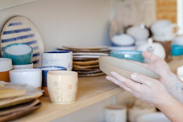 Atelier de poterie. artisan tenant un plat en argile artisanale. concept de vaisselle à la main