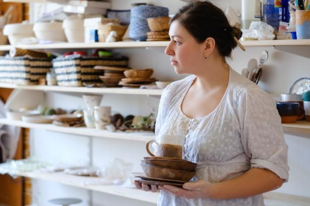 Atelier de poterie. artisan tenant des plats en argile artisanale. concept de vaisselle à la main