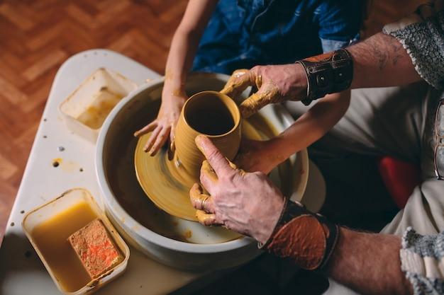 Atelier de poterie. grand-père enseigne la poterie à sa petite-fille. modelage d'argile