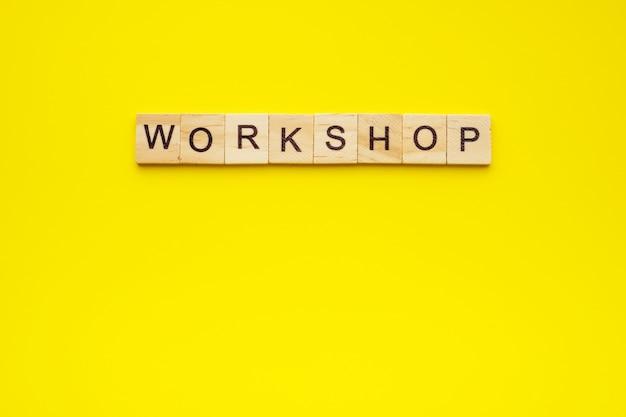 Atelier de texte fait avec des lettres en bois sur jaune