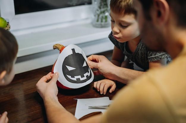Ather et deux enfants découpent un gabarit pour fabriquer une lanterne jack en citrouille orange. image avec mise au point sélective. photo de haute qualité