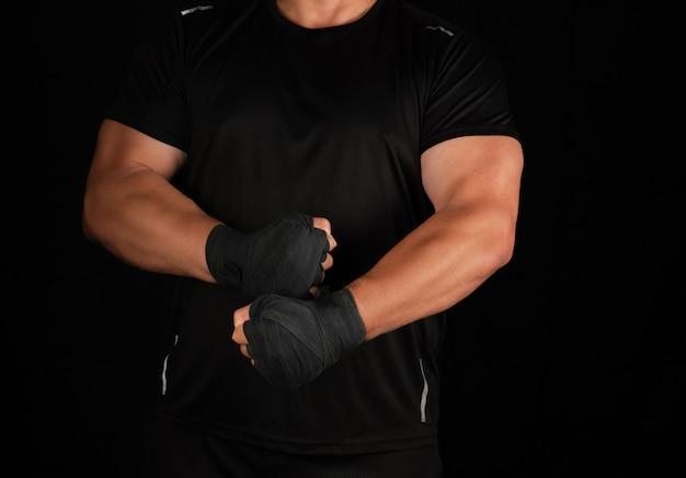 Athlète adulte en uniforme noir est debout dans un rack avec les muscles tendus