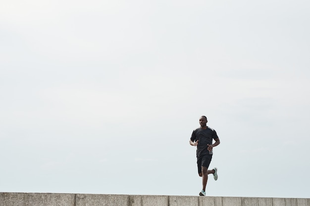 Athlète africain courant le matin dehors contre le ciel bleu