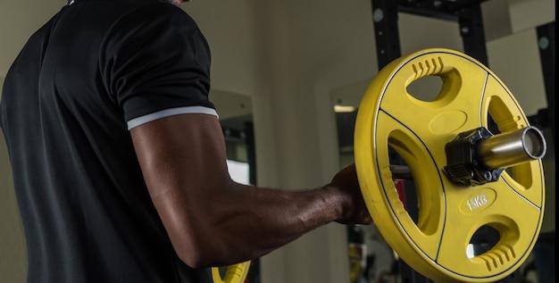 Athlète afro-américain faisant de l'exercice avec une barre dans la salle de sport