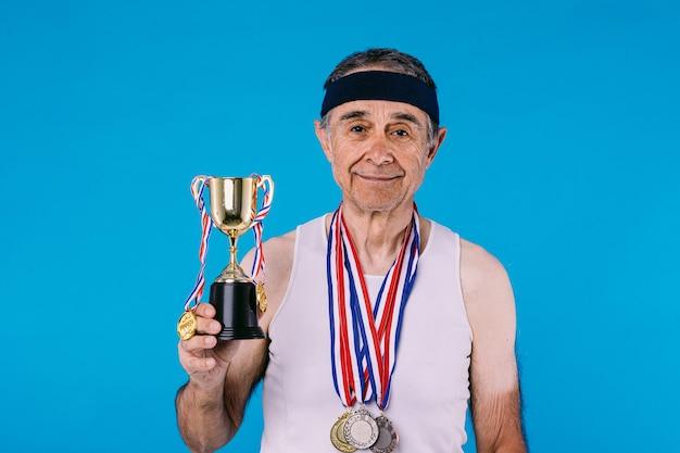 Athlète âgé avec des marques de soleil sur les bras, avec trois médailles au cou tenant un trophée avec des rubans suspendus, sur fond bleu