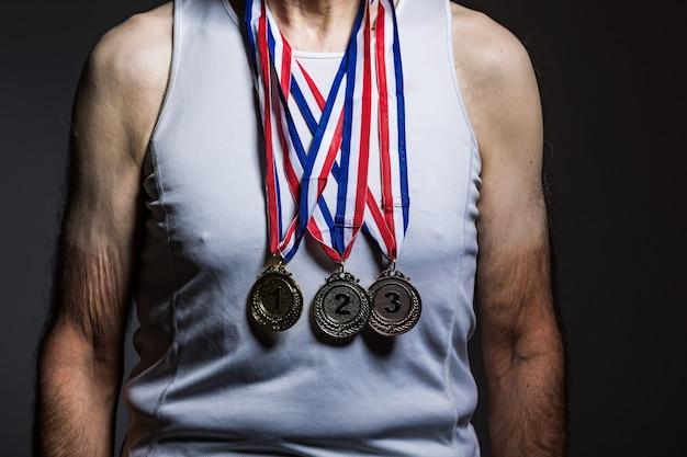 Athlète âgé portant un débardeur blanc, avec des marques de soleil sur les bras, avec trois médailles sur le cou, les montrant, sur un fond sombre. concept de sport et de victoire