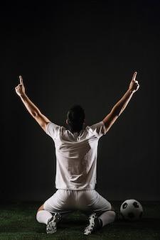 Athlète anonyme pointant vers le haut tout en célébrant la victoire