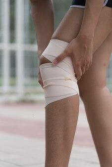 Athlète asiatique assis à côté du stade. elle a eu une blessure au genou et a reçu ses premiers soins.